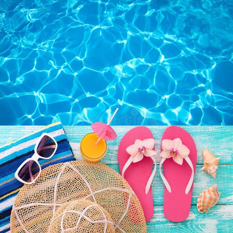 在海滩海滨的暑假 时装配件夏天触发器,帽子,在明亮的绿松石的太阳镜在水池附近上 免版税库存图片