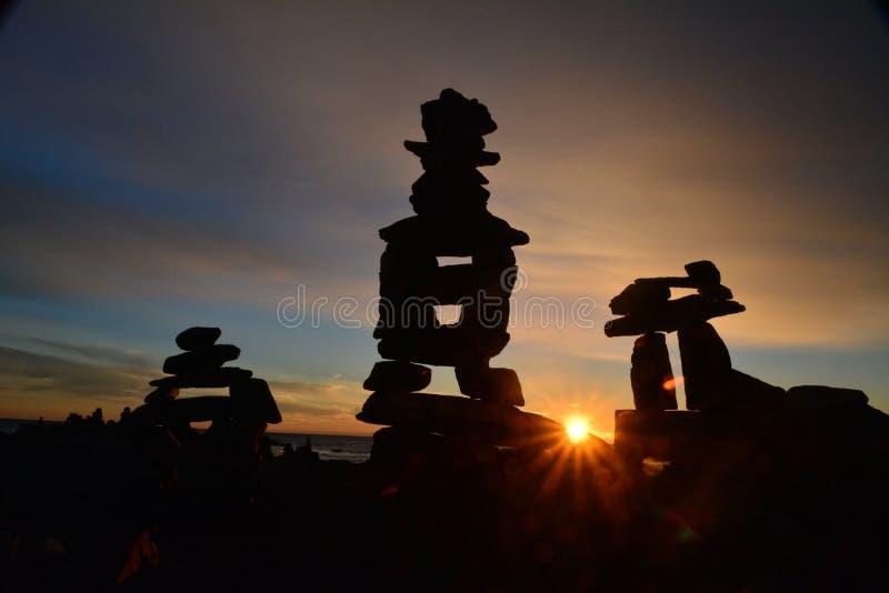 在海洋现出轮廓的岩石石标支持在日出; 库存照片