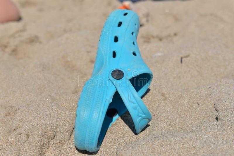 在海滩的一个晴天忘记的孩子的蓝色拖鞋 图库摄影