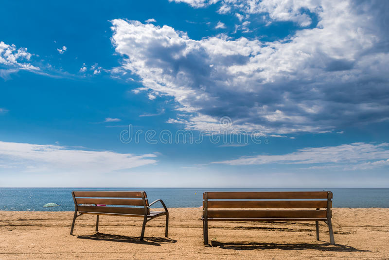 在海滩的两条长凳 免版税库存图片