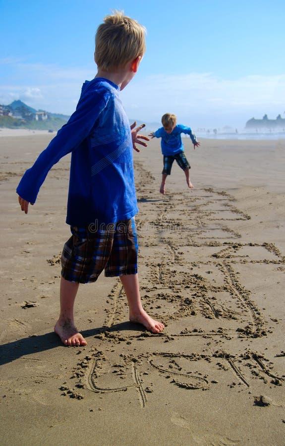 在海滩的儿童游戏跳房子 图库摄影