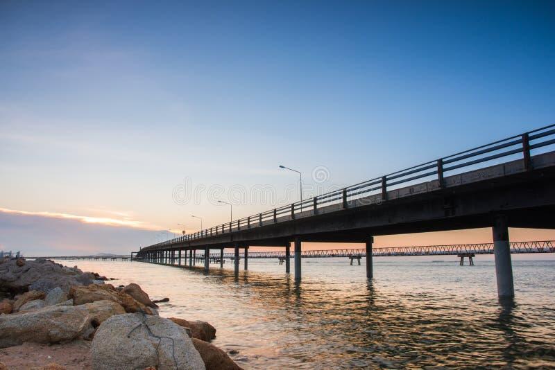 在海水的具体桥梁与日出 免版税库存图片
