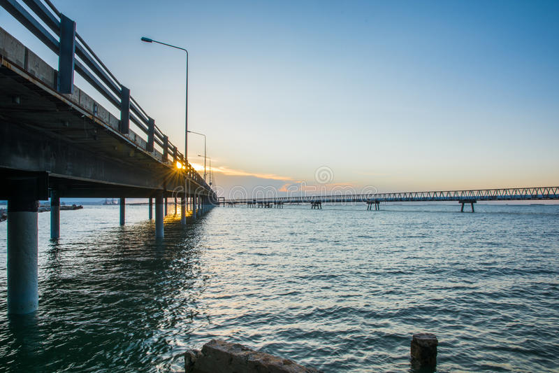 在海水的具体桥梁与日出 免版税库存照片