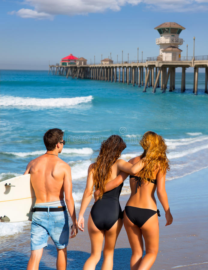在海滩的冲浪者男孩和女孩走的背面图 库存照片