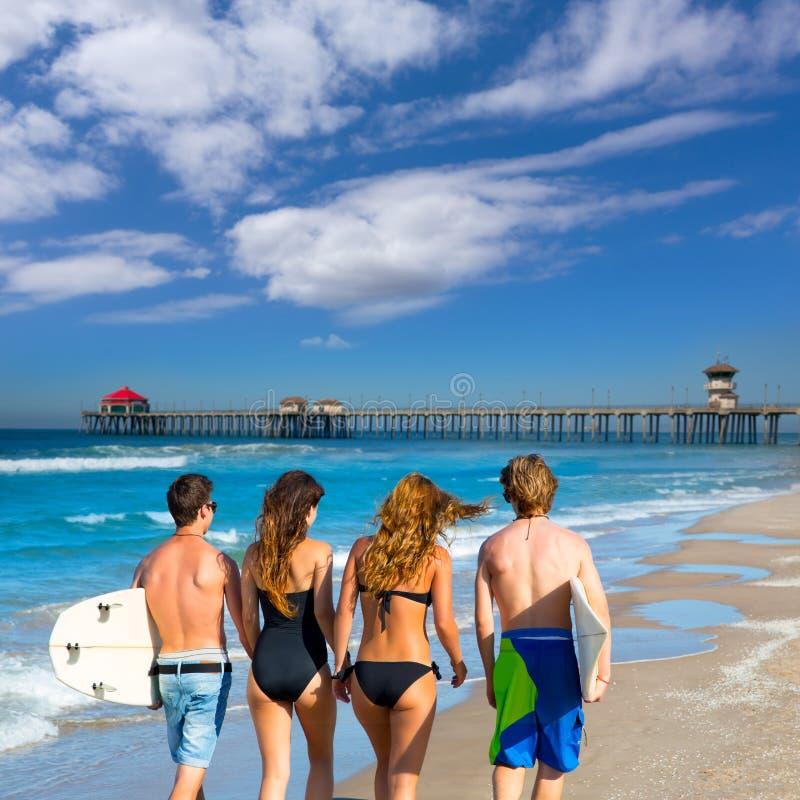 在海滩的冲浪者男孩和女孩走的背面图 免版税库存照片