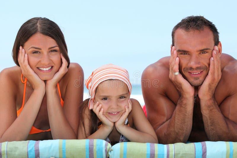 在海滩的可爱的家庭 图库摄影