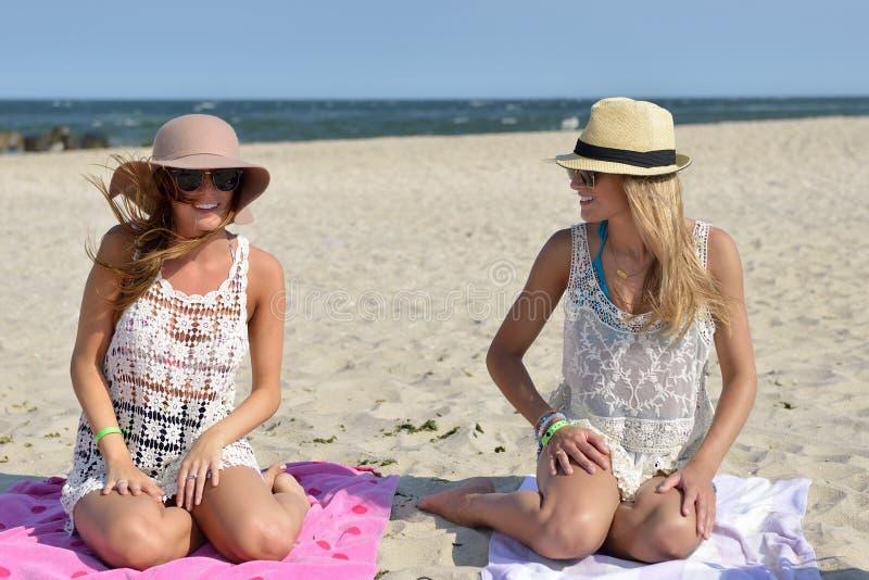 在海滩的天-两名妇女坐沙子 库存图片