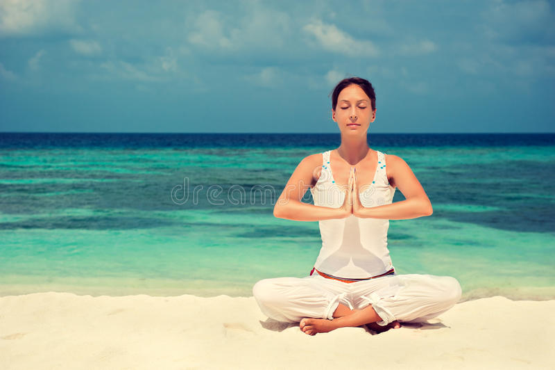 在海滨的女子实践的瑜伽 库存图片