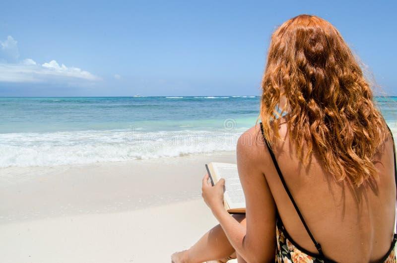 在海滩的女孩读书 库存照片