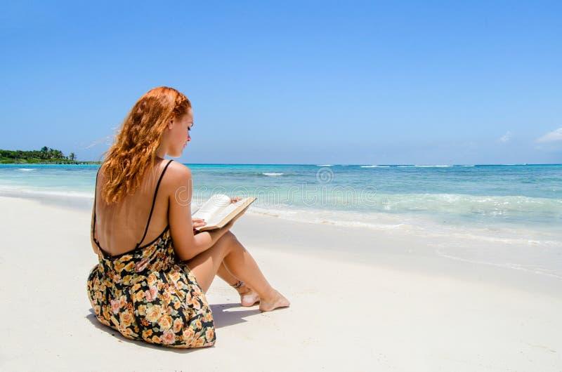在海滩的女孩读书 免版税库存照片