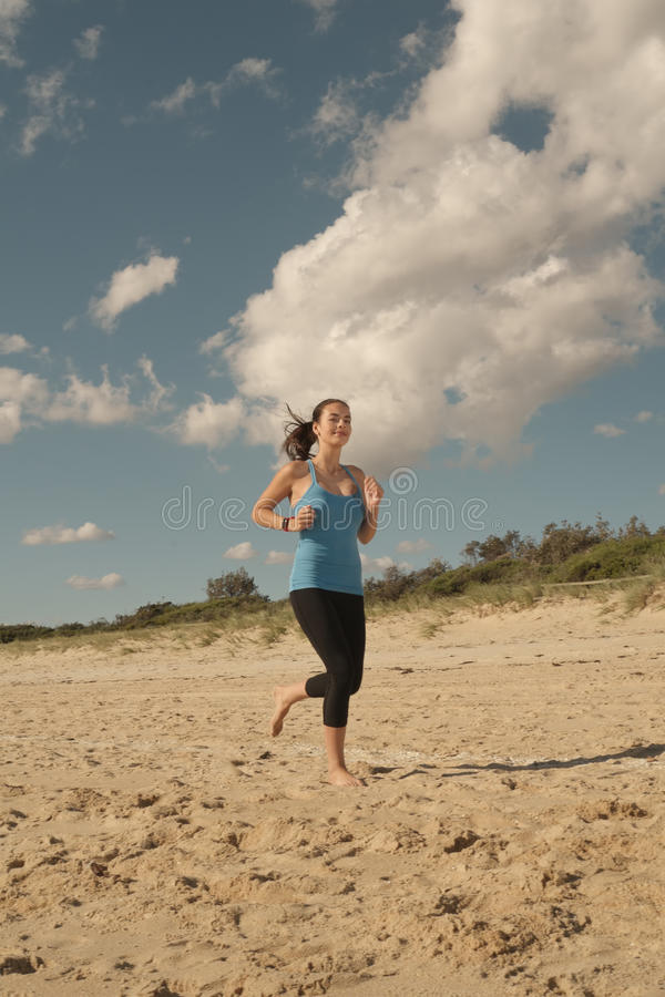 在海滩的妇女奔跑 免版税库存图片