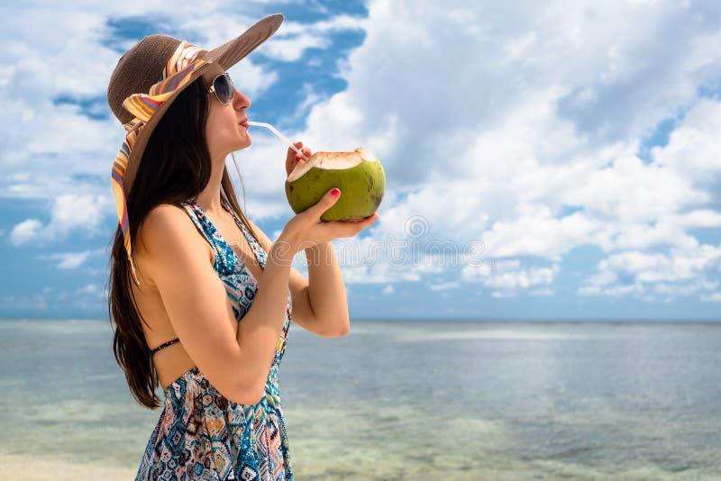 在海滩的妇女旅游饮用的椰奶在假日 图库摄影