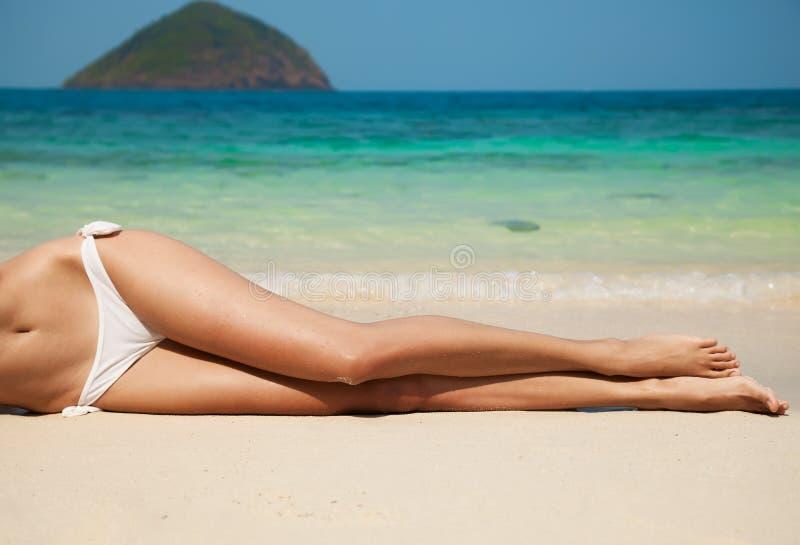 在海滩的妇女的性感的腿 免版税库存图片