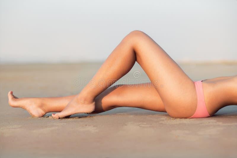 在海滩的妇女` s美好的性感的腿 说谎和放松在海滩沙子的妇女在早晨日落时间 库存照片