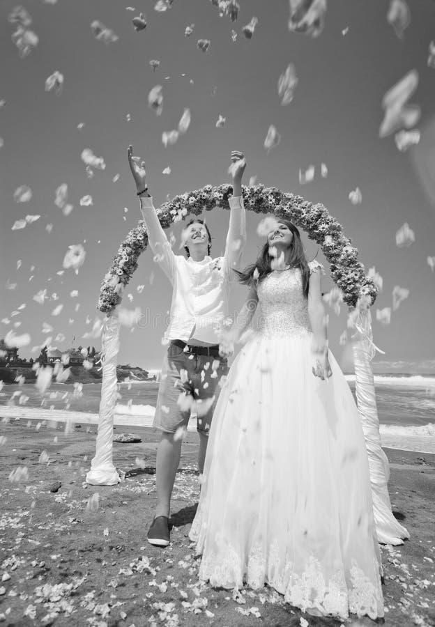 在海滩的婚礼与愉快的蜜月旅行者 库存照片