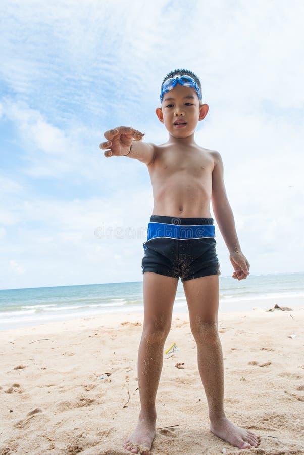 在海滩的嬉戏的男孩和寄居蟹。 免版税库存图片