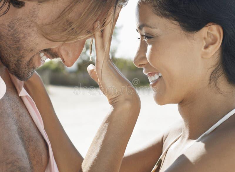在海滩的嬉戏的年轻夫妇 免版税图库摄影