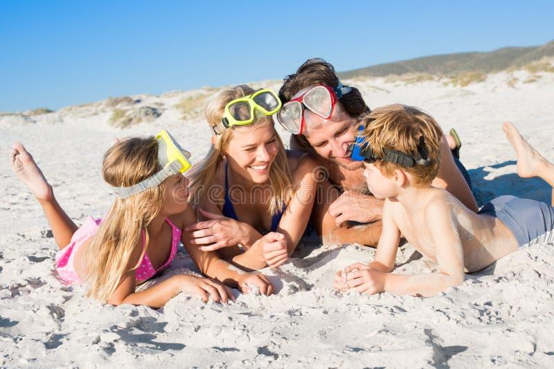 在海滩的家庭与潜航的面具 免版税库存图片