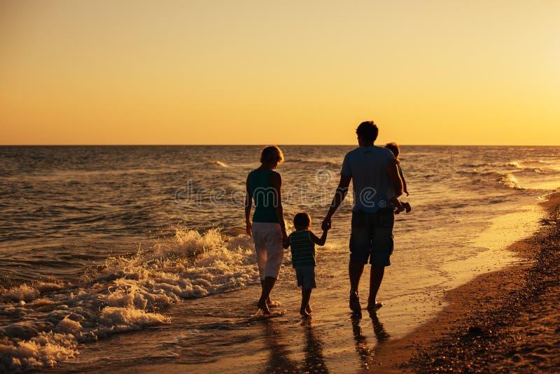 在海滩的家庭剪影在日落 免版税库存照片