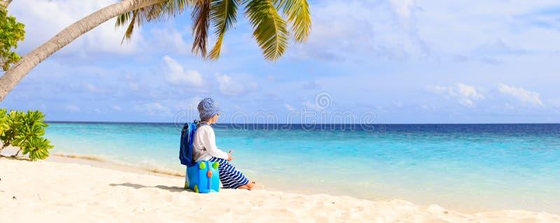 在海滩的小男孩旅行带着手提箱和玩具飞行 库存图片