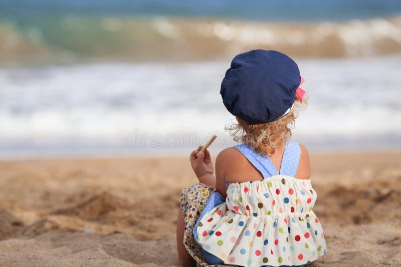 在海滩的小的美丽的愉快的女孩选址 免版税库存图片