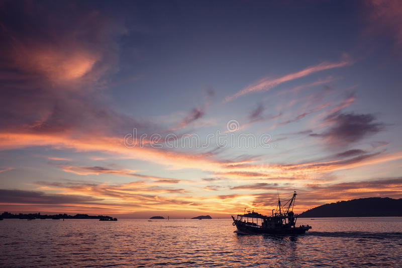 在海洋的小船在日落期间 免版税库存照片