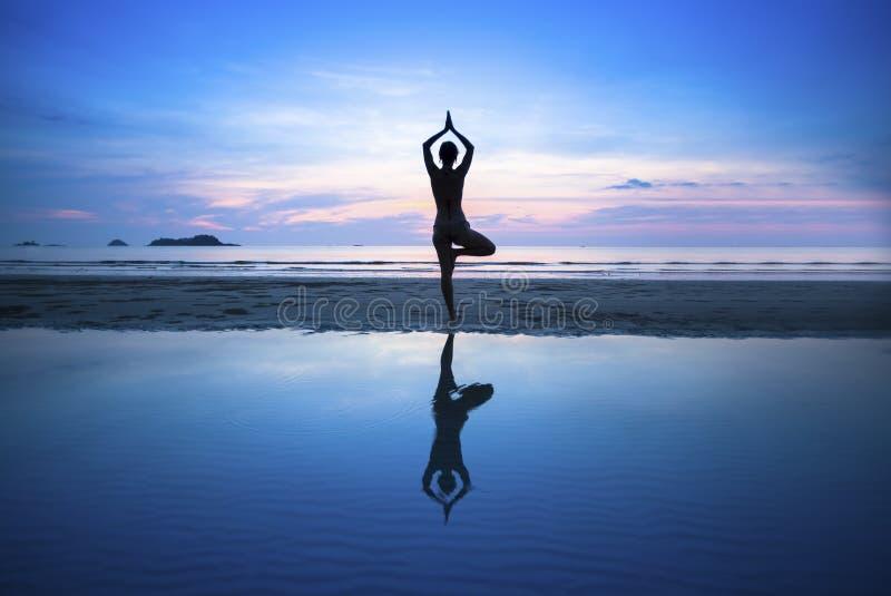 在海滩的少妇实践的瑜伽在超现实主义的日落 库存照片