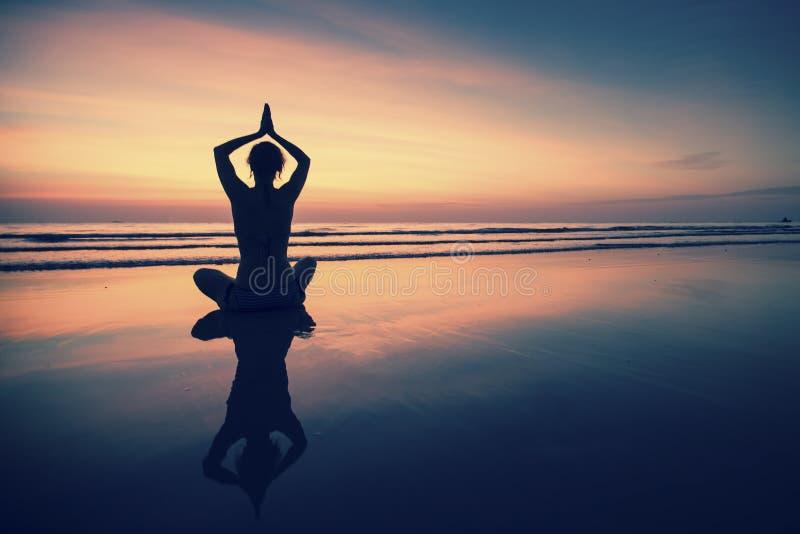 在海滩的少妇实践的瑜伽在超现实主义的日落 免版税库存照片