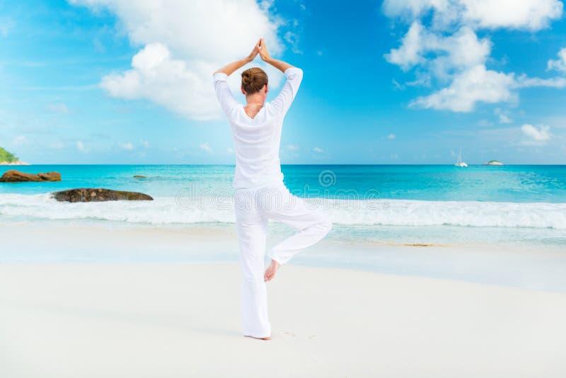 在海滩的少妇实践的瑜伽 库存照片