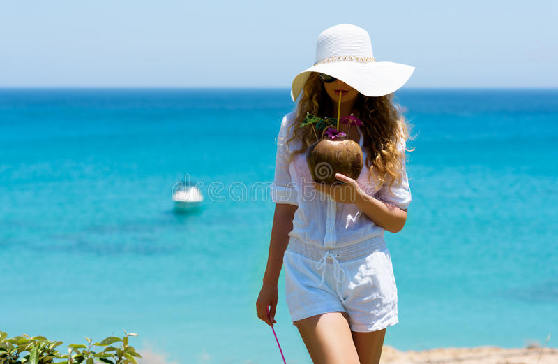在海滩的少妇饮用的椰子鸡尾酒 库存照片