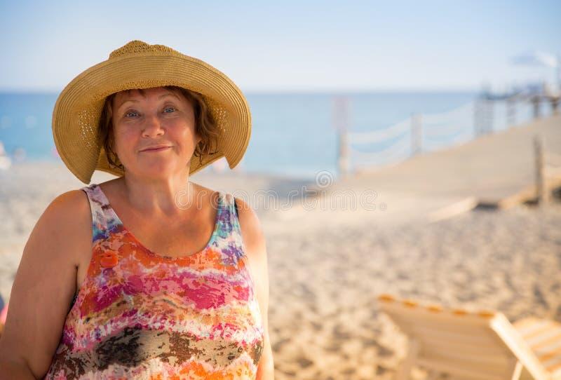 在海滩的微笑的资深妇女佩带的帽子在sunbed 库存照片