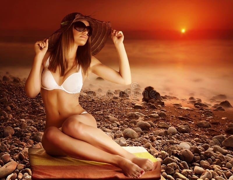 在海滩的性感的模型在日落 免版税库存图片