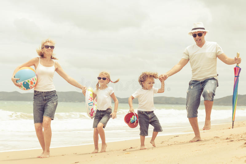 在海滩的愉快的家庭跳舞在天时间 免版税图库摄影