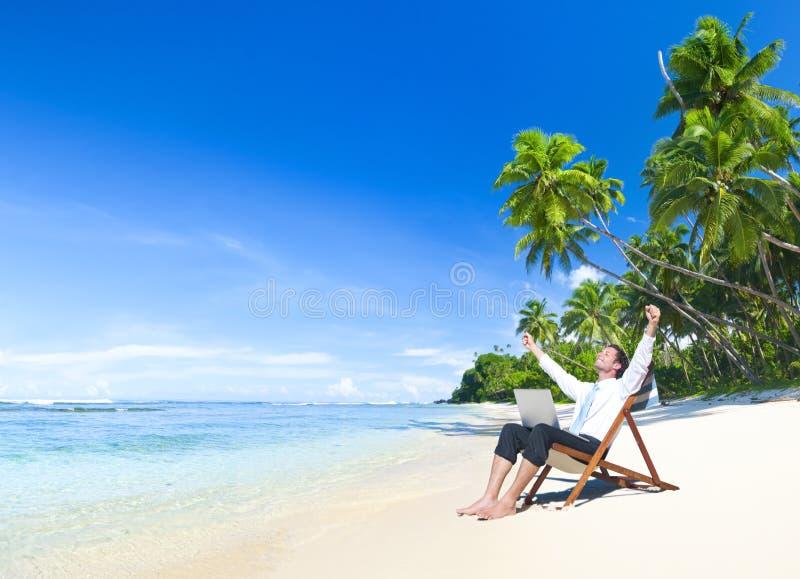 在海滩的愉快的成功的商人 库存照片