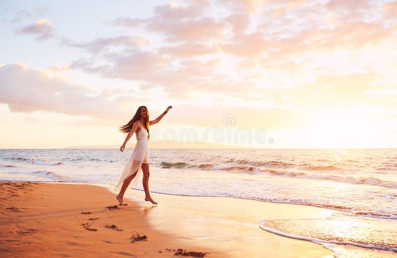 在海滩的愉快的无忧无虑的妇女跳舞在日落 库存照片
