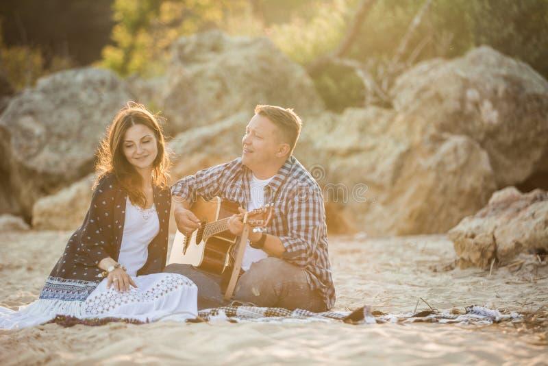 在海滩的成人夫妇 拿着吉他的一个人 库存图片