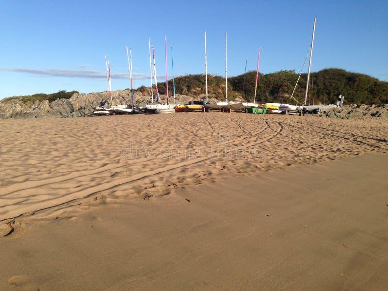 在海滩的日出与帆船 库存照片