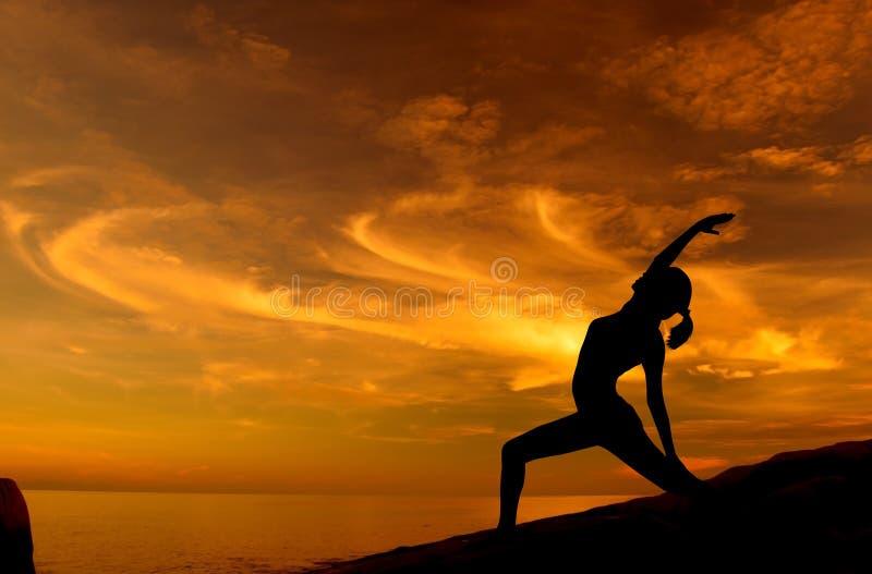 在海滩的日出瑜伽 免版税库存照片