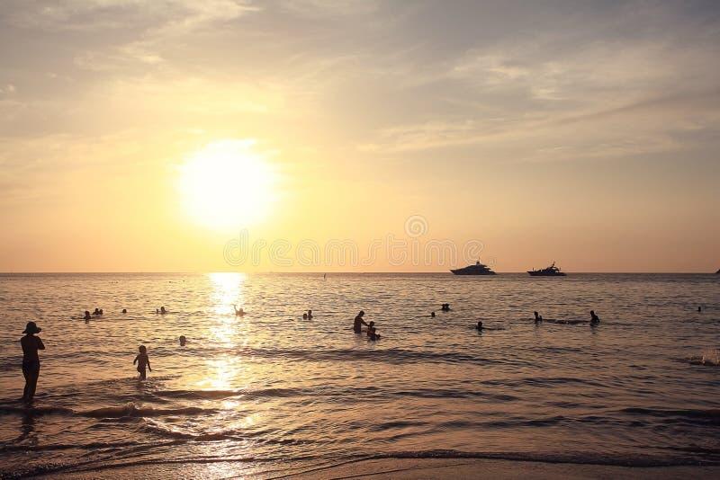 在海滩的日落与人剪影  库存照片