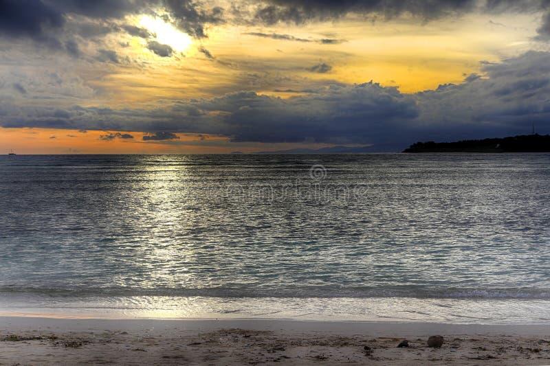 在海洋的日落,云彩太阳,海风,在前景的椰子 在海的明亮的日落 惊人的油漆天空 李 库存照片