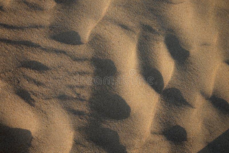 在海滩的日落 在沙子纹理的阴影 免版税库存照片