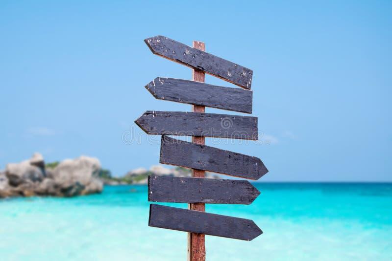 在海滩的木标志 海和蓝天背景木头标志 图库摄影