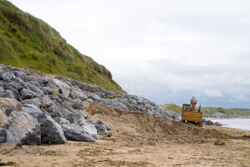 在海滩的机械挖掘机 库存图片