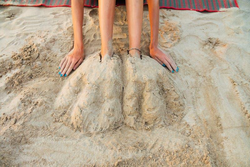 在海滩的沙子埋葬的腿美丽的少妇 沙子性感的坐的妇女 免版税库存图片