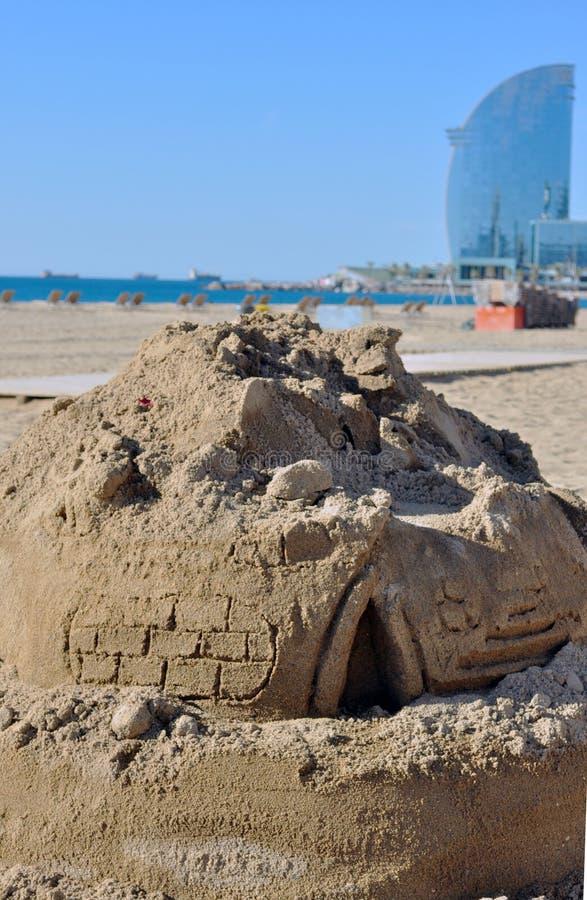 在海滩的沙子城堡与背景大厦 免版税库存图片