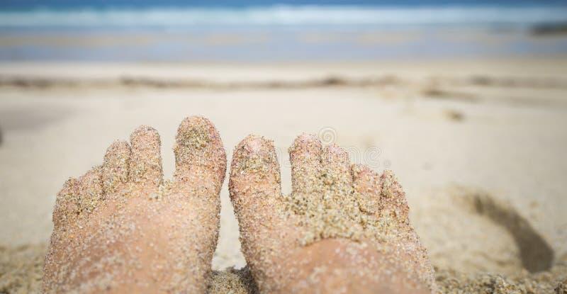 在海滩的沙子的妇女脚与海水的我 免版税图库摄影