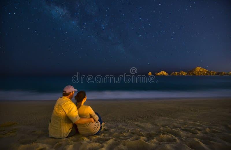 在海滩的浪漫夫妇在晚上在Cabo圣卢卡斯墨西哥 免版税库存图片