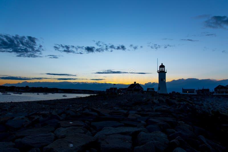 在海滩的灯塔在日落 免版税库存照片
