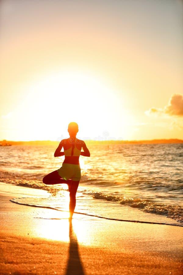 在海滩的瑜伽健身妇女实践的树姿势在日落 免版税库存照片