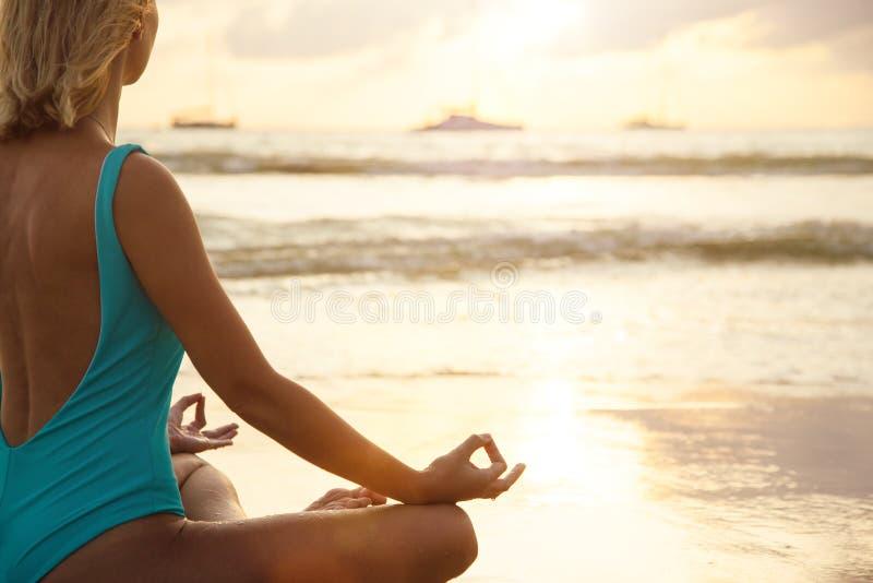 在海滩的瑜伽在日落的水附近 免版税库存图片